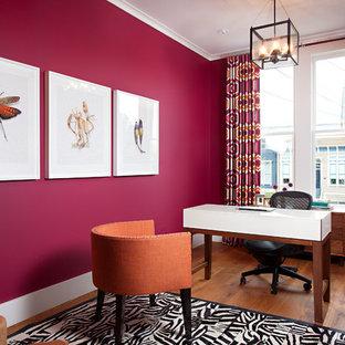 Aménagement d'un bureau rétro de taille moyenne avec un mur rose, un sol en bois brun, un bureau indépendant, aucune cheminée et un sol marron.