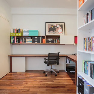 Small trendy built-in desk medium tone wood floor and brown floor study room photo in New York with white walls and no fireplace
