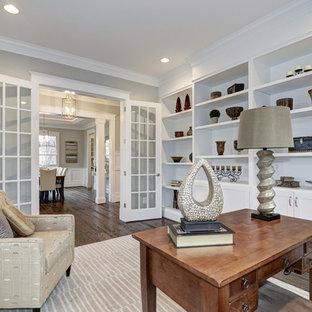 Modelo de despacho de estilo americano, de tamaño medio, con paredes grises, suelo de madera oscura y escritorio independiente
