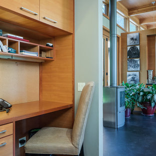 This is an example of a medium sized modern home office and library in Seattle with green walls, concrete flooring, a metal fireplace surround and a built-in desk.