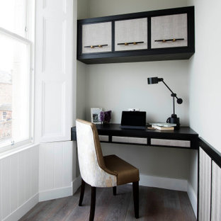 Inspiration for a traditional study in Other with grey walls, medium hardwood flooring, a built-in desk and brown floors.