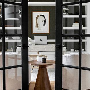 Diseño de despacho minimalista, de tamaño medio, con paredes blancas, suelo de madera clara, escritorio independiente y suelo marrón