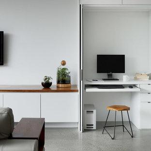 Неиссякаемый источник вдохновения для домашнего уюта: кабинет среднего размера в современном стиле с белыми стенами, бетонным полом, встроенным рабочим столом и серым полом