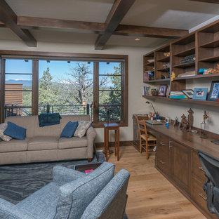 Idee per un ufficio stile americano con pavimento in legno massello medio, camino ad angolo, cornice del camino in pietra e scrivania incassata