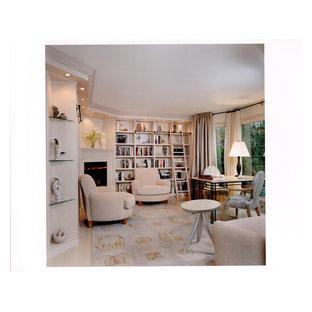 Klassisk inredning av ett stort arbetsrum, med ett bibliotek, beige väggar, ljust trägolv, en öppen hörnspis, en spiselkrans i sten och ett fristående skrivbord