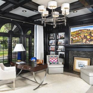 タンパの中くらいのトランジショナルスタイルのおしゃれな書斎 (黒い壁、濃色無垢フローリング、標準型暖炉、石材の暖炉まわり、自立型机、茶色い床、格子天井、壁紙) の写真