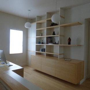 Diseño de despacho moderno, de tamaño medio, sin chimenea, con paredes blancas, escritorio independiente y suelo de bambú