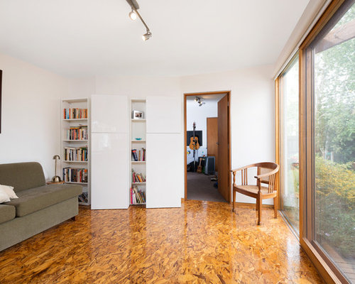 trendy brown floor home office photo in melbourne with white walls