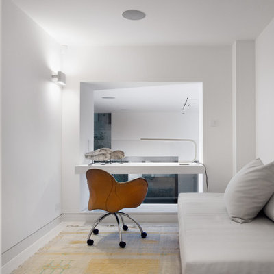 Mid-sized trendy built-in desk study room photo in London with white walls