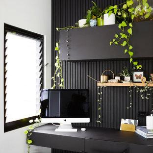 Foto på ett litet funkis arbetsrum, med svarta väggar och ett inbyggt skrivbord