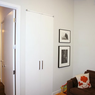Trendy dark wood floor home office photo in New York with white walls