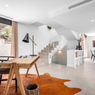 Diseño de despacho mediterráneo, sin chimenea, con paredes blancas, escritorio independiente y suelo beige