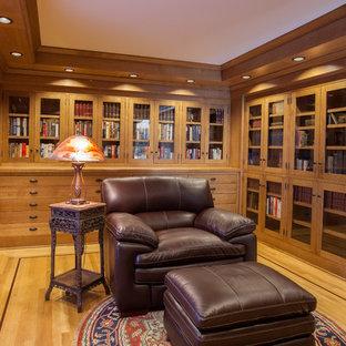 Esempio di uno studio stile americano di medie dimensioni con libreria, pareti marroni, parquet chiaro, scrivania autoportante e pavimento marrone