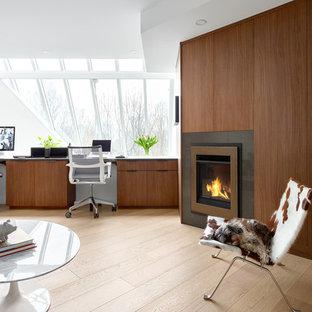Foto på ett stort funkis hemmabibliotek, med vita väggar, ljust trägolv, en standard öppen spis, en spiselkrans i trä, ett inbyggt skrivbord och brunt golv