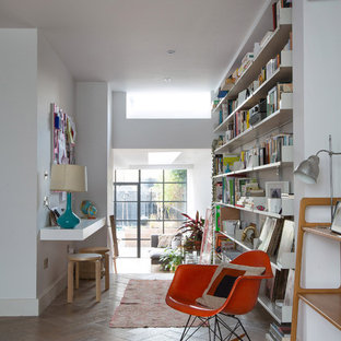 This is an example of a large contemporary home office and library in London with white walls, medium hardwood flooring and a built-in desk.