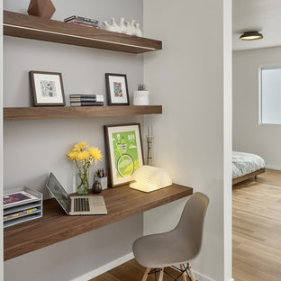 Design ideas for a small midcentury study room in San Francisco with white walls, light hardwood floors and a built-in desk.