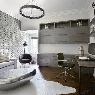 Пример оригинального дизайна: рабочее место среднего размера в современном стиле с встроенным рабочим столом, белыми стенами, темным паркетным полом и кирпичными стенами без камина