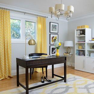 Idee per un atelier minimal di medie dimensioni con pareti grigie, pavimento in bambù, scrivania autoportante e pavimento marrone