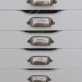 トロントの中サイズのトランジショナルスタイルのおしゃれなクラフトルーム (白い壁、無垢フローリング、コーナー設置型暖炉、造り付け机、茶色い床) の写真