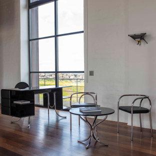 コペンハーゲンの広い北欧スタイルのおしゃれな書斎 (白い壁、無垢フローリング、自立型机、茶色い床、レンガ壁、三角天井) の写真
