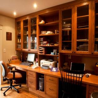 Diseño de despacho de estilo americano, de tamaño medio, sin chimenea, con paredes beige, suelo de madera en tonos medios y escritorio empotrado