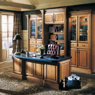ボストンの中くらいのトラディショナルスタイルのおしゃれなホームオフィス・書斎 (ライブラリー、青い壁、レンガの床、標準型暖炉、漆喰の暖炉まわり、自立型机、ベージュの床) の写真