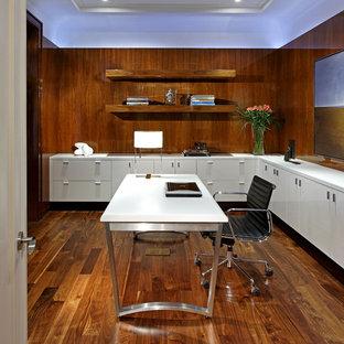 Пример оригинального дизайна: большое рабочее место в современном стиле с темным паркетным полом, отдельно стоящим рабочим столом, коричневыми стенами и коричневым полом без камина