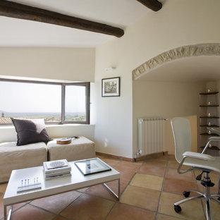 Неиссякаемый источник вдохновения для домашнего уюта: кабинет в средиземноморском стиле с белыми стенами, отдельно стоящим рабочим столом и полом из терракотовой плитки