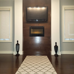 Example of a mid-sized minimalist freestanding desk dark wood floor and brown floor study room design in Toronto with gray walls, a standard fireplace and a wood fireplace surround