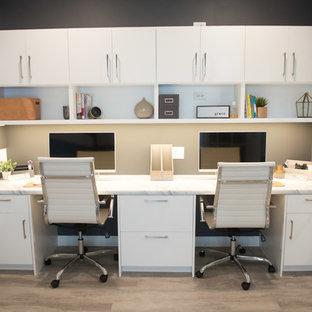 他の地域の大きいモダンスタイルのおしゃれなホームオフィス・仕事部屋 (グレーの壁、ラミネートの床、造り付け机、グレーの床) の写真