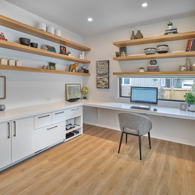 Example of a trendy built-in desk light wood floor study room design in Edmonton with white walls and no fireplace