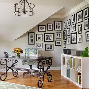Foto de despacho clásico con paredes grises, suelo de madera clara y escritorio independiente