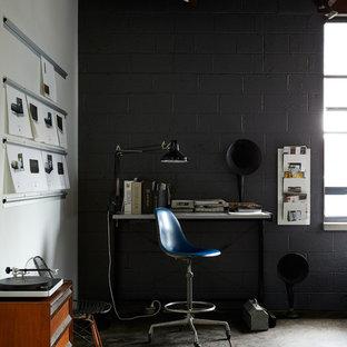 ニューヨークのインダストリアルスタイルのおしゃれなホームオフィス・仕事部屋 (黒い壁、コンクリートの床、自立型机、グレーの床) の写真