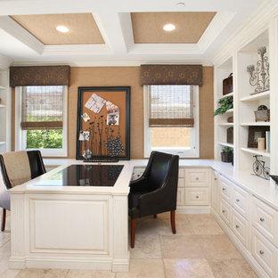 Elegant built-in desk beige floor home office photo in Orange County