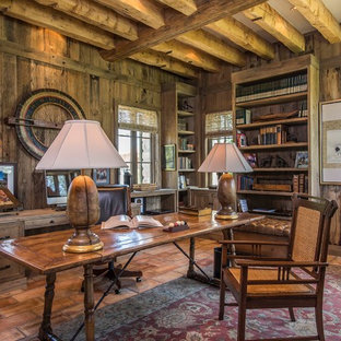 This is an example of a large study in Phoenix with brown walls, terracotta flooring, no fireplace, a stone fireplace surround and a freestanding desk.