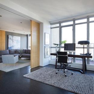 バンクーバーのコンテンポラリースタイルのおしゃれな書斎 (白い壁、暖炉なし、自立型机、黒い床) の写真