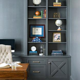 Exempel på ett stort klassiskt hemmabibliotek, med grå väggar, mörkt trägolv, ett fristående skrivbord och brunt golv