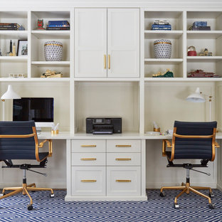 Foto di uno studio tradizionale con pareti bianche, moquette, scrivania incassata e pavimento blu