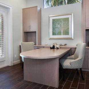 На фото: рабочее место среднего размера в стиле модернизм с полом из керамической плитки, встроенным рабочим столом и серыми стенами