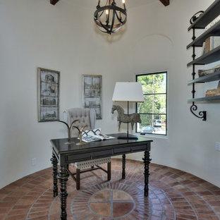 Immagine di un ufficio mediterraneo di medie dimensioni con pareti bianche, pavimento in terracotta, scrivania autoportante e nessun camino