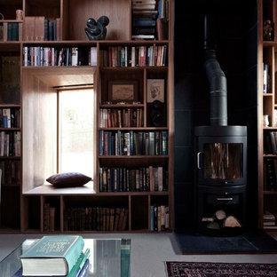 Ispirazione per un piccolo ufficio contemporaneo con pareti marroni, moquette, stufa a legna, cornice del camino in pietra, scrivania autoportante e pavimento beige