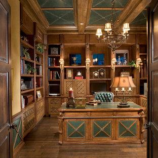 フェニックスの広い地中海スタイルのおしゃれなホームオフィス・書斎 (ライブラリー、無垢フローリング、自立型机、茶色い床) の写真
