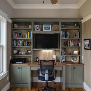 Diseño de despacho de estilo americano, de tamaño medio, sin chimenea, con suelo de madera en tonos medios, paredes beige, escritorio empotrado y suelo marrón