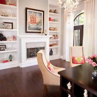 Idéer för mellanstora funkis arbetsrum, med grå väggar, ett fristående skrivbord, en standard öppen spis, mellanmörkt trägolv och brunt golv