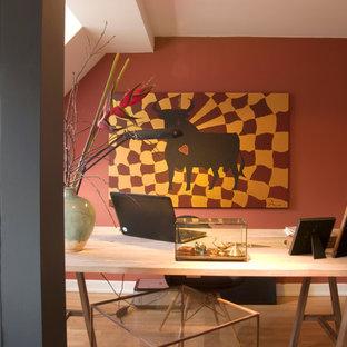 Idee per uno studio eclettico con pareti rosse, pavimento in legno massello medio e scrivania autoportante