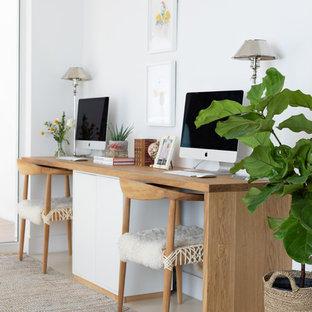 マイアミの中サイズのビーチスタイルのおしゃれな書斎 (白い壁、コンクリートの床、自立型机、ベージュの床) の写真