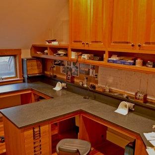 Foto på ett stort amerikanskt hemmabibliotek, med beige väggar, mörkt trägolv, ett inbyggt skrivbord och brunt golv