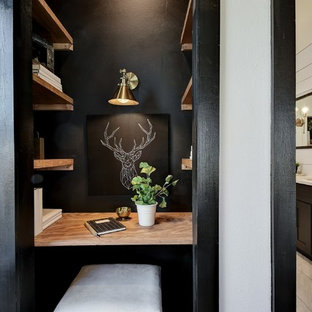 Example of a mid-sized trendy built-in desk home office design in Austin with black walls