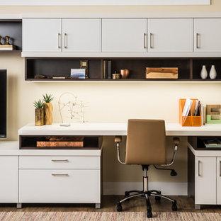 Immagine di un ufficio minimal di medie dimensioni con pareti beige, pavimento in laminato, nessun camino, scrivania autoportante e pavimento marrone