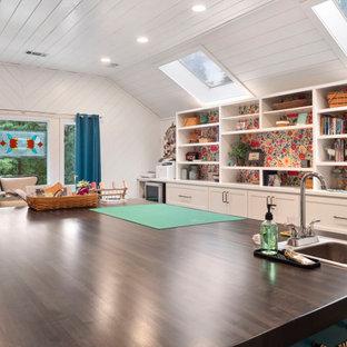 Großes Retro Nähzimmer mit weißer Wandfarbe, Vinylboden, Einbau-Schreibtisch, braunem Boden, Holzdielendecke und Holzdielenwänden in Atlanta